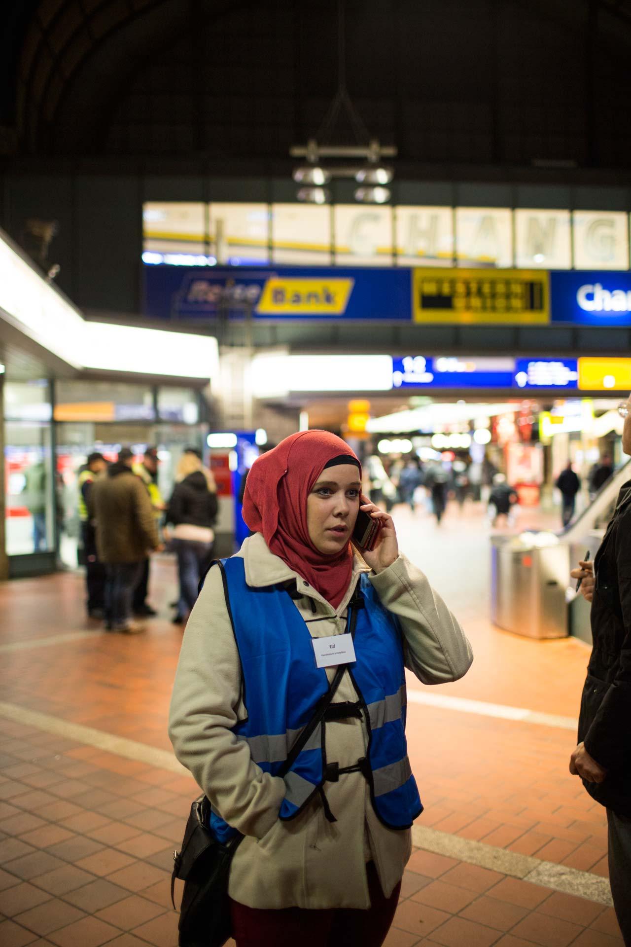 Seit vielen Monaten nehmen ehrenamtliche Helfer am Hamburger Hauptbahnhof Flüchtlinge in Empfang. Die freiweillige Helferin Tomke Bittu (Elif) versucht telefonisch herauszufinden, wo in dieser Nacht noch Schlafplätze für Transitflüchtlinge frei sind. Foto: Philipp Reiss