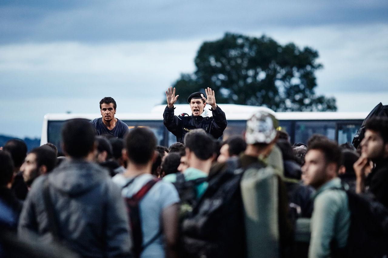 Ein österreichischer Polizist versucht, Flüchtlinge zu beruhigen, die bei Heiligenkreuz an der Grenze von Ungarn nach Österreich warten. Foto: Roland Geisheimer