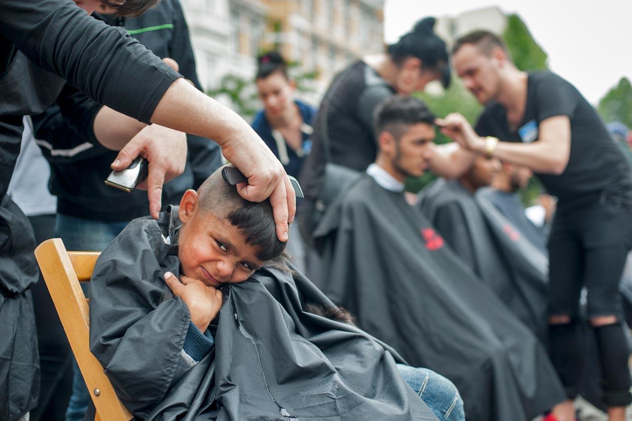 Die »Herzlichen Haarschneider« schneiden Flüchtlingen, die in der Hamburger Messehalle 6 eine erste Unterkunft gefunden haben, auf Wunsch gratis die Haare. Foto: Martin Langer