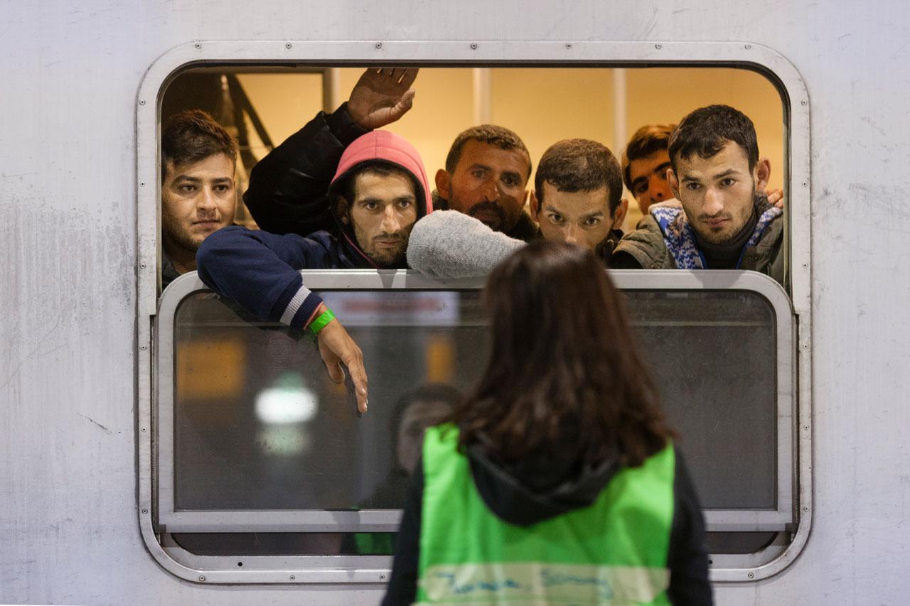 Aus der Serie »Drehscheibe Köln« – Eine Dolmetscherin begrüßt einige der 710 Flüchtlinge, die soeben mit einem Sonderzug der Deutschen Bahn aus Passau am Bahnhof des Koeln/Bonner Flughafens angekommen sind. Foto: Bernd Lauter