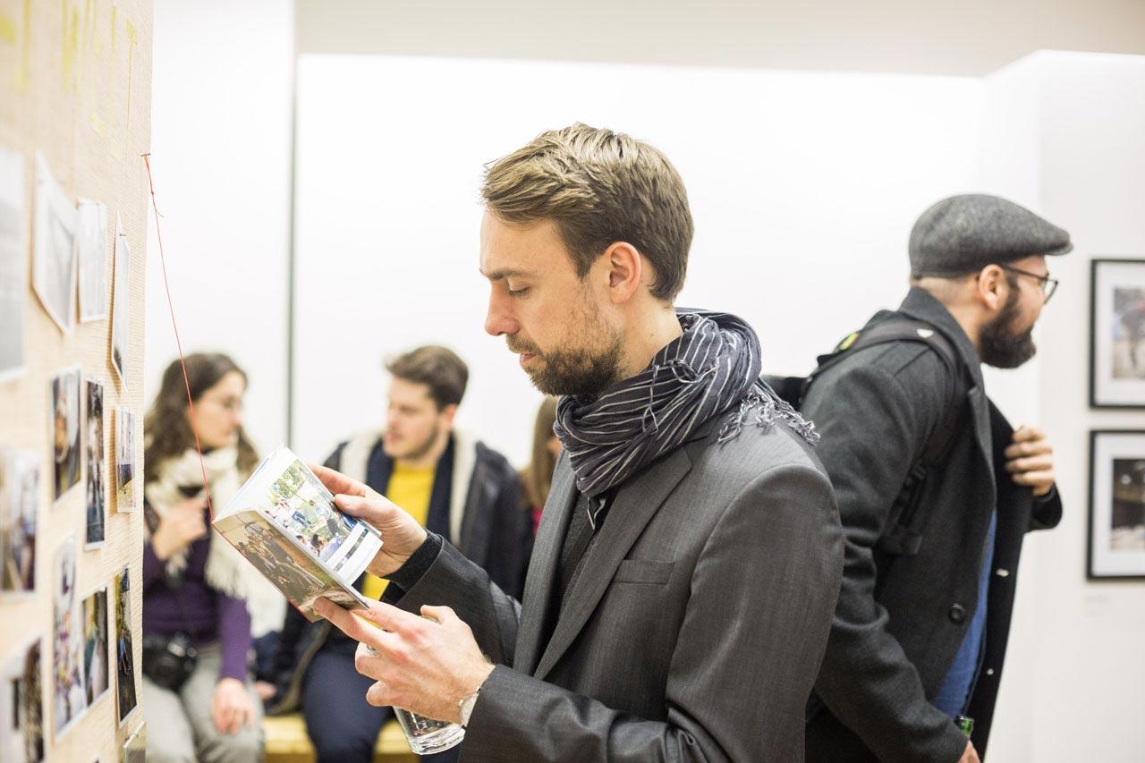 Philipp Reiss studiert die Informationen zum Fotoprojekt mit jugendlichen Flüchtlingen von Nora Klein.